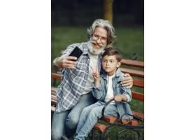男孩和爷爷坐在长凳上一家人在公园里老_10063073