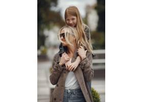 夏日城市里时髦的母亲带着女儿_9659472