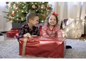 孩子们在有圣诞树的房子里拿着一份很大的圣_9931824