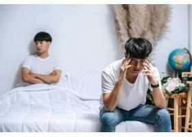 两个年轻人在床上生气另一个坐在床边压_10040239