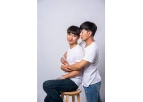 两个相爱的男人拥抱在一起坐在椅子上_10039443