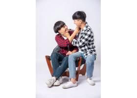 两个相爱的男人拥抱在一起坐在椅子上_10039967