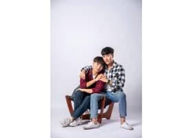 两个相爱的男人拥抱在一起坐在椅子上_10039976