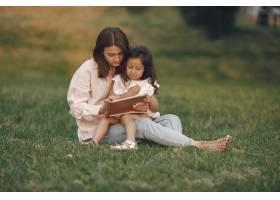 优雅的母亲带着女儿在夏季公园里_9658818