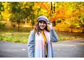 美丽的女孩走在秋日大街上的肖像_8471571