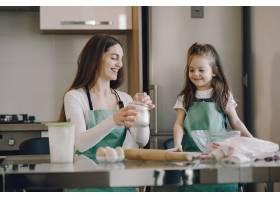 母亲和女儿把面团煮成饼干_8355473