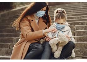 母亲带着女儿戴着口罩走在外面_7710662
