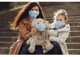 母亲带着女儿戴着口罩走在外面_7710663