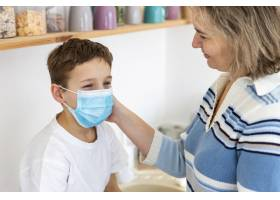 母亲给孩子戴上医用口罩_7747673