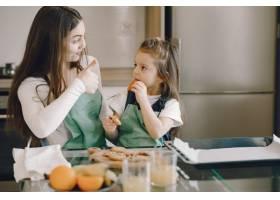 母女俩坐在厨房里吃饼干_8355505