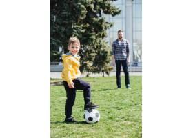 可爱的男孩和他的父亲在公园里踢足球_7927334