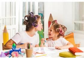 这位年轻的母亲和她的小女儿在家里用铅笔作_9060076