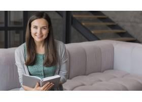 面带微笑的女人坐在沙发上看书_8218099