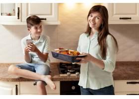 母子俩在厨房里端着食物_9266455