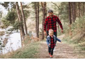 父亲带着年幼的儿子在树林里_7869785