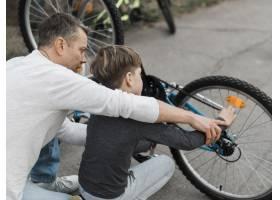 父亲教他的儿子把自行车放在肩上修理_7733465