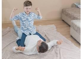父亲节儿子坐在爸爸身上玩耍_7732847