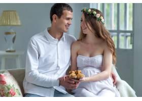 快乐的年轻夫妇穿着婴儿鞋坐在家里_8049707