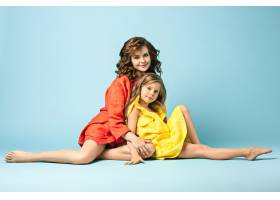 怀孕的母亲和十几岁的女儿蓝色背景上的家_7911250