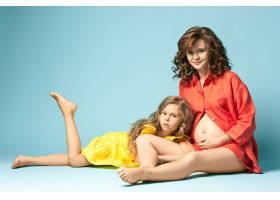 怀孕的母亲和十几岁的女儿蓝色背景上的家_7911252