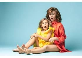 怀孕的母亲和十几岁的女儿蓝色背景上的家_9060055