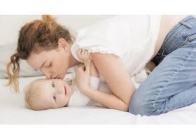 成年母亲亲吻她的女婴_7936857
