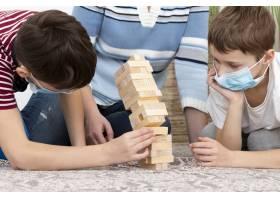 戴着医用口罩的孩子和母亲一起玩Jenga_7747088