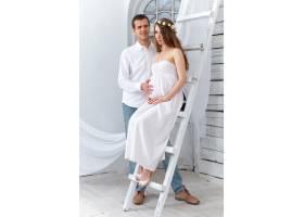 欢快的年轻夫妇穿着白色衣服站在家里_8049712