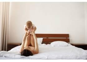 年轻快乐的母亲在家里的床上陪着她刚出生的_9028536