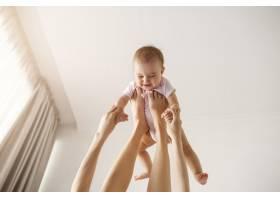 年轻快乐的母亲在家里的床上陪着她刚出生的_9028543