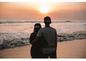 年轻浪漫情侣走在海滩上的剪影肖像女孩和_8270052
