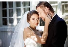 年轻漂亮的新婚夫妇微笑着享受着拥抱着_7599918