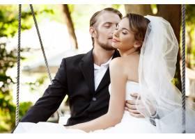 年轻漂亮的新婚夫妇微笑着亲吻着坐在公_7599794