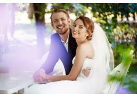 年轻漂亮的新婚夫妇微笑着拥抱着坐在户_7599924