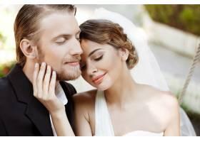 年轻漂亮的新婚夫妇闭着眼睛微笑享受着_7599797