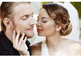 年轻漂亮的新婚夫妇闭着眼睛微笑享受着_7599799