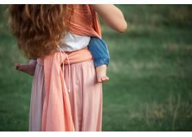 年轻漂亮的母亲在户外拥抱她蹒跚学步的儿子_8821648