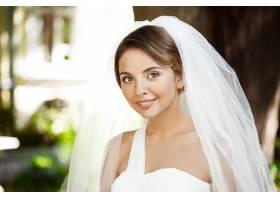 年轻漂亮的金发新娘穿着婚纱戴着面纱微笑_7599785