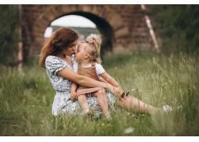 年轻的母亲带着小女儿坐在公园的草地上_8827788