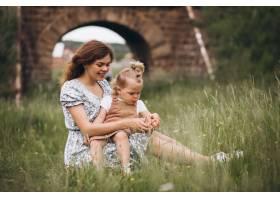 年轻的母亲带着小女儿坐在公园的草地上_8827789