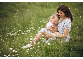 年轻的母亲带着小女儿坐在公园的草地上_8827793