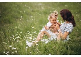 年轻的母亲带着小女儿坐在公园的草地上_8827794