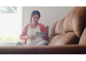 年轻的亚洲孕妇使用平板电脑搜索怀孕信息_6139083