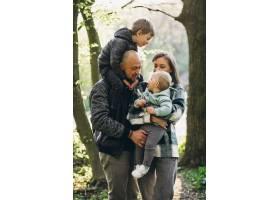 年轻的家庭带着他们的孩子在森林里玩耍_8380504