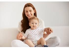 年轻的母亲和她一岁的小儿子穿着睡衣正在放_10271374