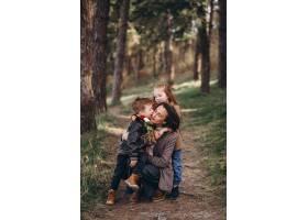 年轻的母亲带着女儿和儿子在森林里_7869883