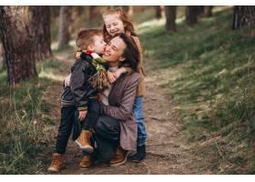 年轻的母亲带着女儿和儿子在森林里_7869885
