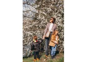 年轻的母亲带着女儿和儿子在森林里_7869898