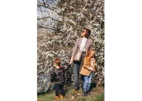 年轻的母亲带着女儿和儿子在森林里_786989802