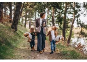 年轻的母亲带着女儿和儿子在森林里_7869902